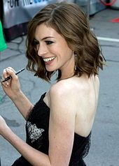 a picture of anne hathaway smiling to her right and holding a pen in her right