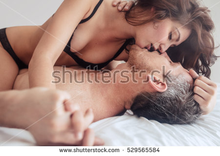stock photo young couple being intimate kissing on bed sensual lovers making love in bedroom